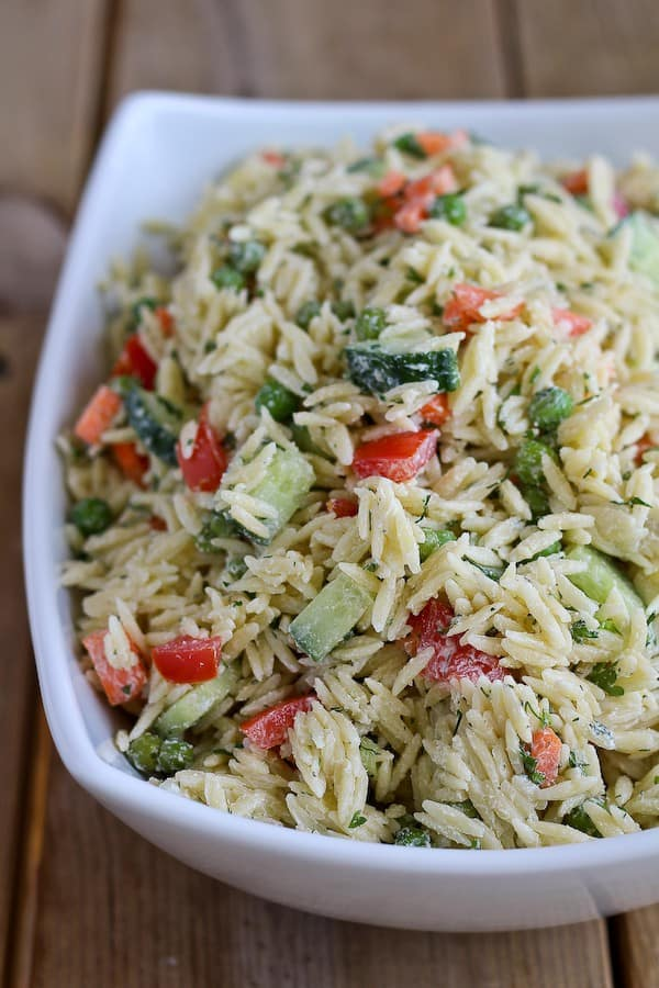 Large white bowl on a wooden background, full of colorful orzo pasta salad with dill.