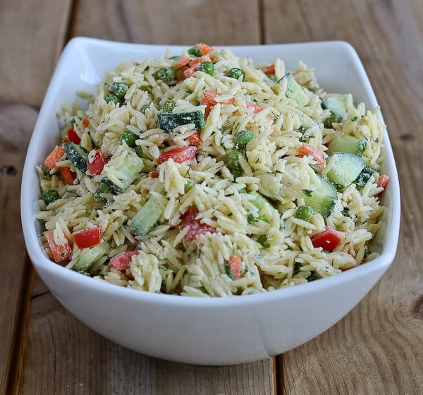 Close up view of an orzo pasta salad with dill dressing in a white bowl