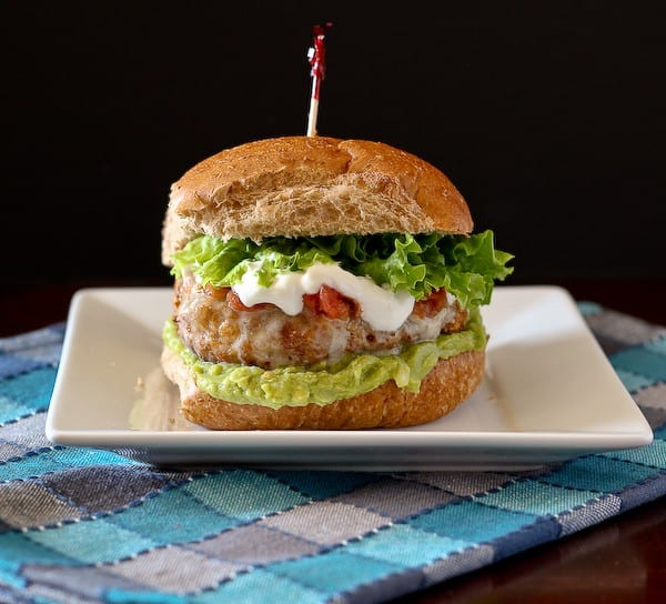 Front view of turkey burger on bun with toppings on white plate, with blue plaid cloth.