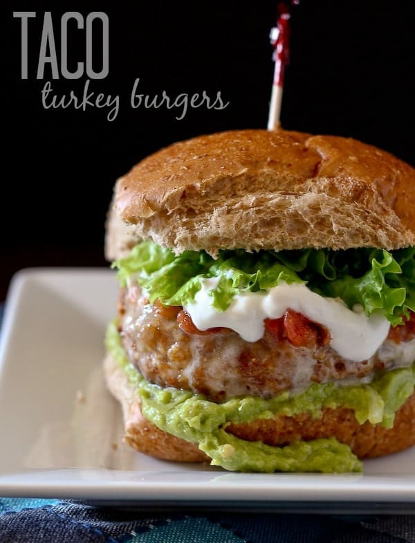 """Front view of turkey burger on bun with toppings on square white plate. Text overlay reads """"Taco turkey burgers."""""""
