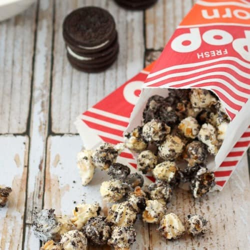 Oreo popcorn spilling from red and white popcorn bag.