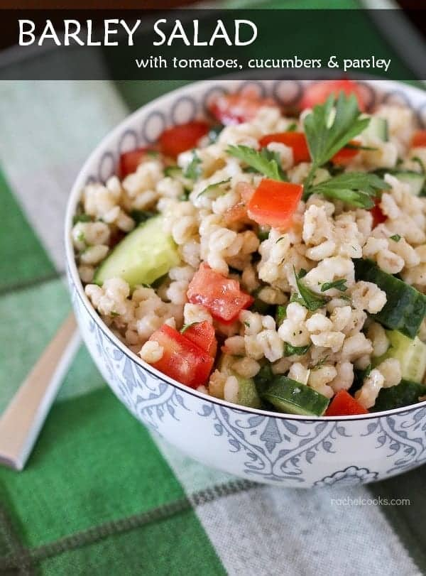 "Front view of salad in a patterned blue and white bowl. Text overlay reads ""Barley Salad with tomatoes, cucumbers & parsley."""