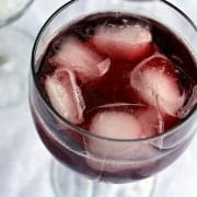 Close up overhead view of red wine spritzer in clear wine glass with 5 ice cubes.