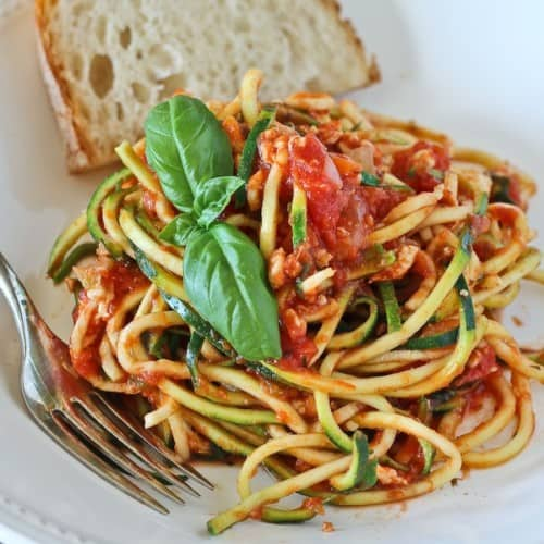 Turkey bolognese with zucchini noodles in white bowl with fork and bread.
