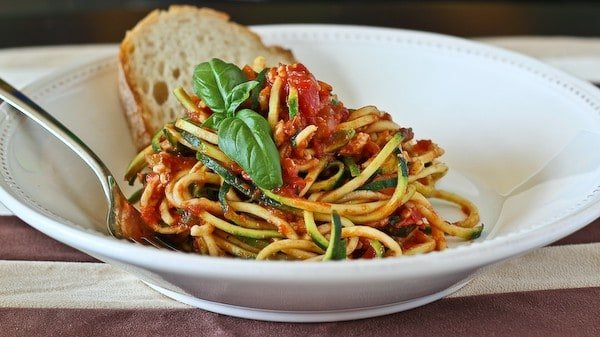 Front view of turkey bolognese on bowl with fork, garnished with fresh basil.