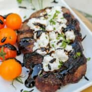 Goat cheese topped steak with balsamic drizzle, with tomatoes and parsley on white plate.