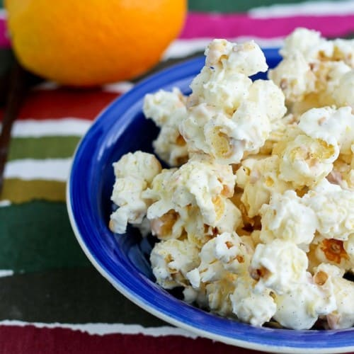 Popcorn in shallow blue bowl with orange in background.