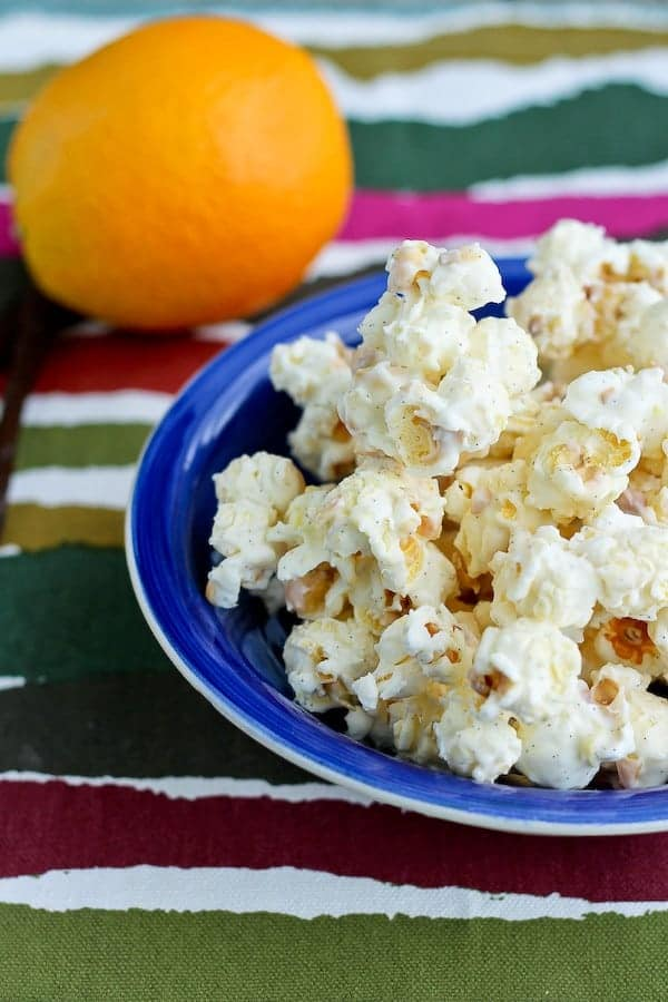 Partial image of popcorn in blue bowl, orange in background.