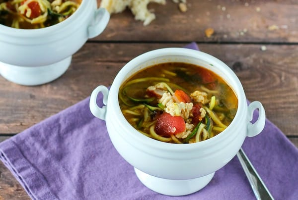 Image of Italian Turkey Soup with Zucchini Noodles in white bowl with purple fabric and spoon .