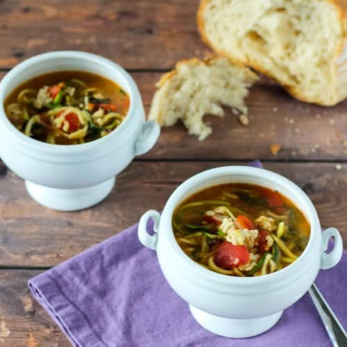 Turkey soup in small white pedestal bowls with rustic bread.