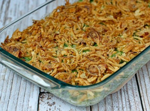 Partial image of clear glass baking dish containing green bean casserole.