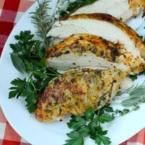 Overhead of sliced turkey breast on white oval platter garnished with fresh herbs.