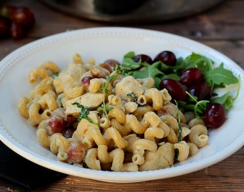 Pasta in shallow white bowl, garnished with fresh arugula and grapes.