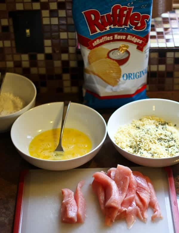 Photo showing the breading process with bag of Ruffles Potato Chips in background.