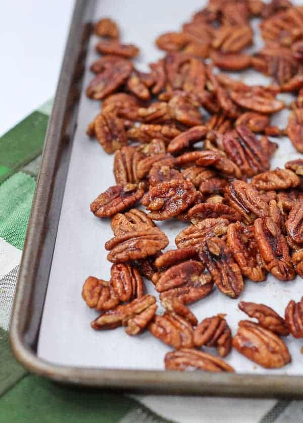 Partial image of spiced pecans cooling on baking pan lined with parchment.