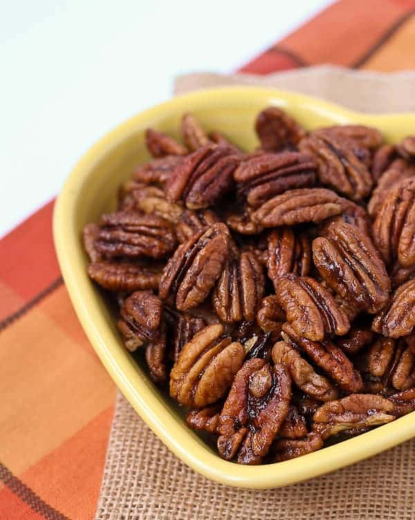 Partial image of spiced pecans in yellow heart shaped bowl, on burlap and orange plaid background.