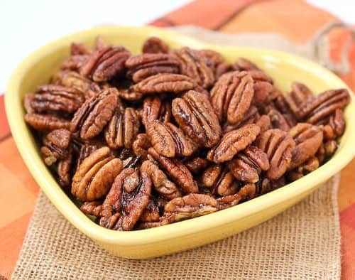 Partial front view of spiced pecans in yellow heart shaped bowl.