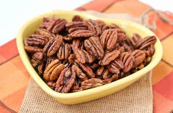 Front view of spiced pecans in yellow heart shaped bowl.