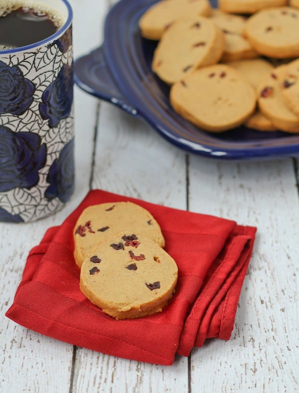 Two cookies on folded red napkin with tall mug of coffee and more cookies in background.