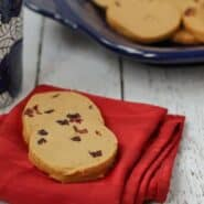 Front view of 2 gingerbread shortbread cookies on folded red napkin.