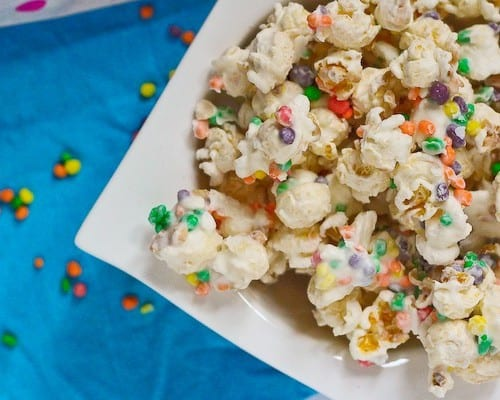 Bowl of nerds popcorn on bright blue background with candy scattered around.