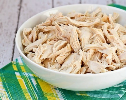 Shallow white dish containing shredded cooked chicken.
