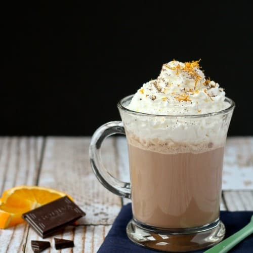 Front view of hot chocolate in clear glass mug, garnished with whipped cream, and orange zest.