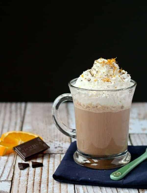 Front view of clear glass mug containing hot chocolate garnished with whipped cream, and orange zest, and placed on a folded black napkin.