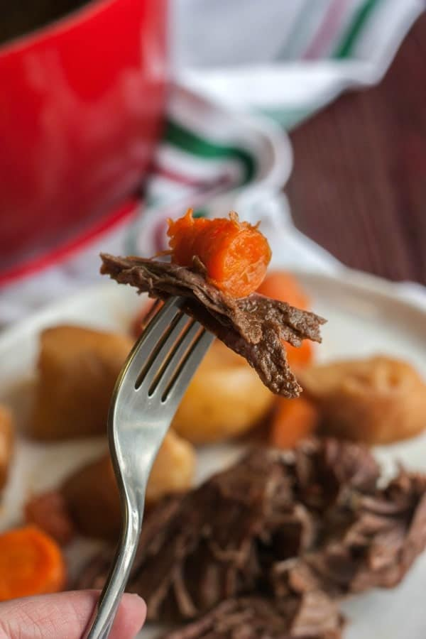 Closeup of fork with a piece of pot roast and a slice of carrot on the tines. In the background is a plate of pot roast dinner.