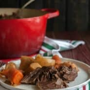 Close up of plated pot roast chunks, with carrots and potatoes behind it. In the background is red Dutch oven with serving spoon.