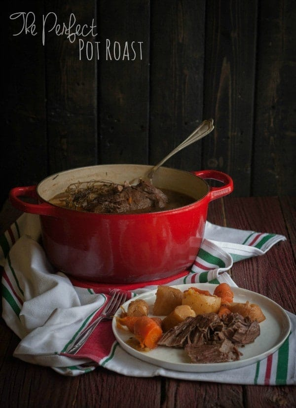 "Image of plated pot roast dinner on round white plate in foreground, red Dutch oven in background with serving spoon, both on a red and green striped dish towel. Also in the image is a text overlay that reads ""The perfect pot roast."""