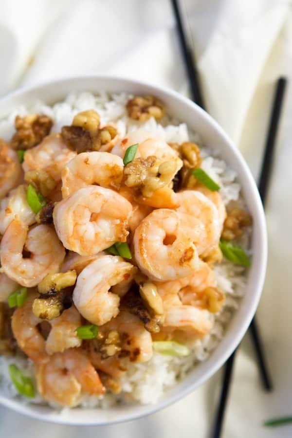 Overhead of honey walnut shrimp in white bowl, on white cloth.