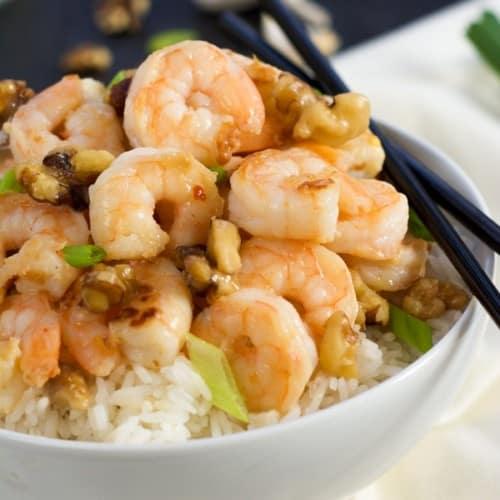 honey walnut shrimp on rice in round white bowl with black chopsticks.
