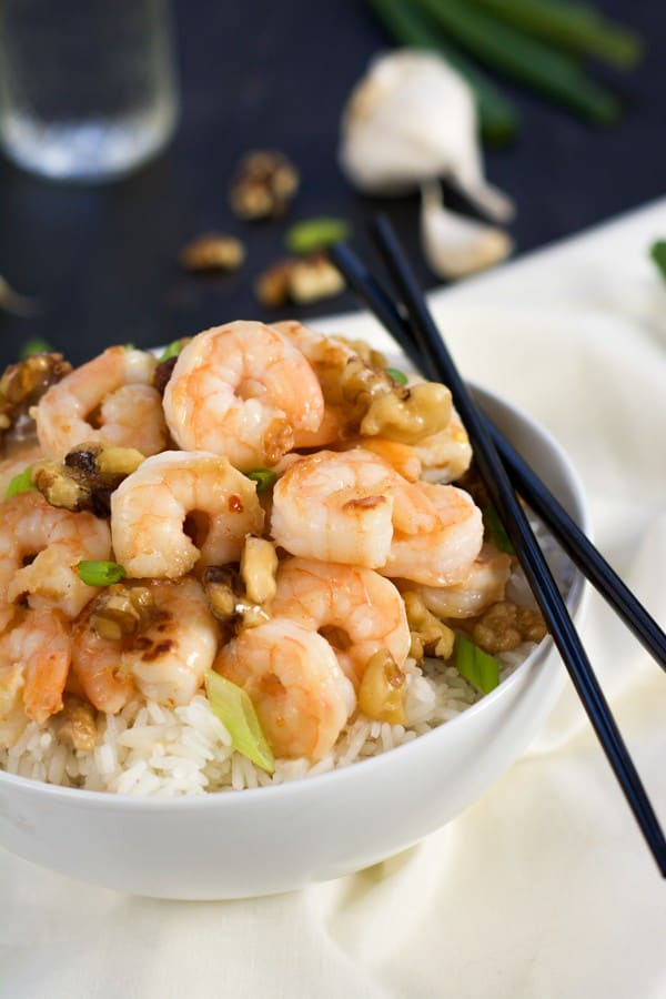 Honey walnut shrimp served in white bowl with black chopsticks.