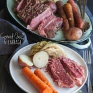"A white plate, containing corned beef slices, 2 carrots, red skinned potato cut in half, and cabbage. Included in the image is oval platter with remaining sliced corned beef, vegetables, with serving utensils. Also in the image is a text overlay that reads "" corned beef & cabbage."""