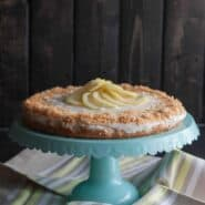 Coconut lemon cake displayed on pedestal cake stand, with striped cloth underneath and dark background.
