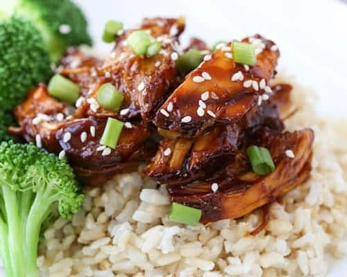 Closeup of chicken teriyaki garnished with green onion and sesame seeds.