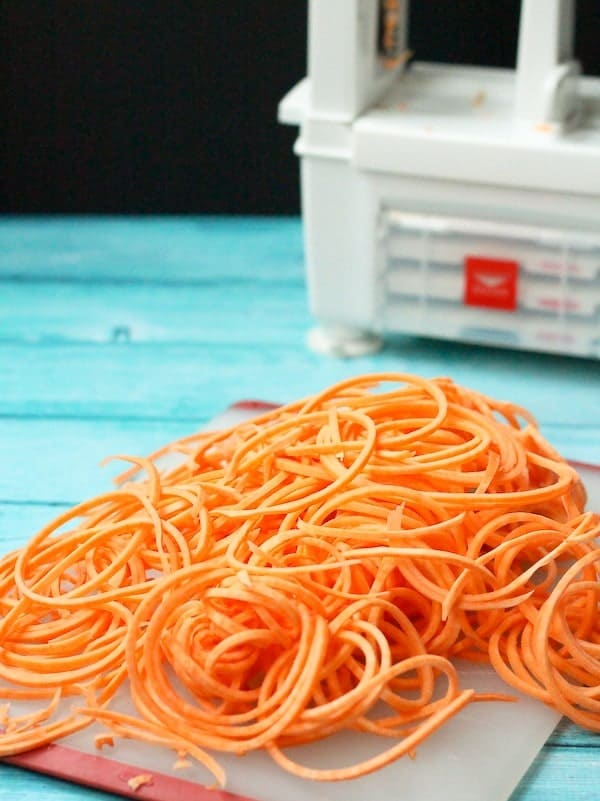 In the foreground, a pile of sweet potato noodles rests on an acrylic cutting board, with a partial picture of a spiralizer in the background.