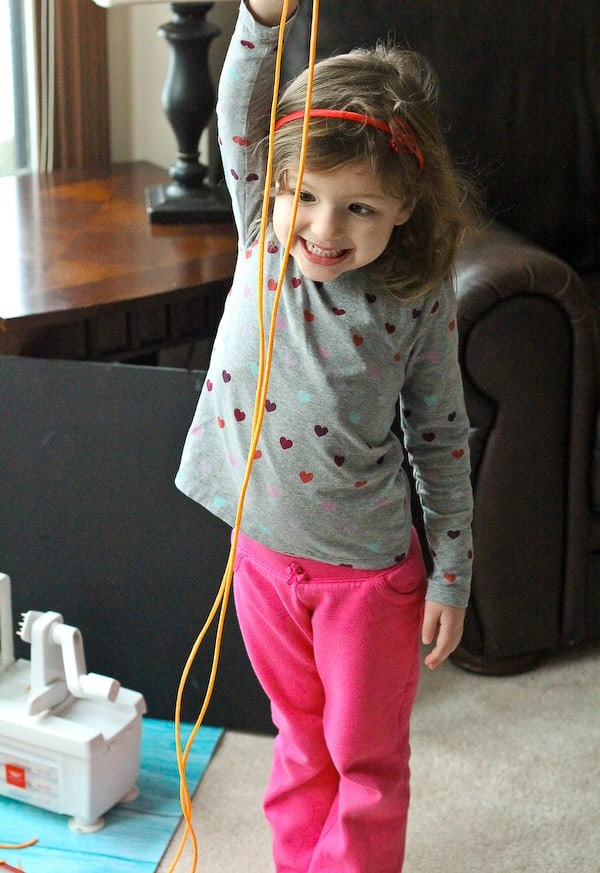 Pictured is a toddler girl, in a living room, holding a very long straight sweet potato noodle, demonstrating how long it is--taller than she is!
