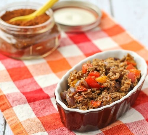 A serving of taco meat in brown oval dish, with small jar of taco seasoning in background.