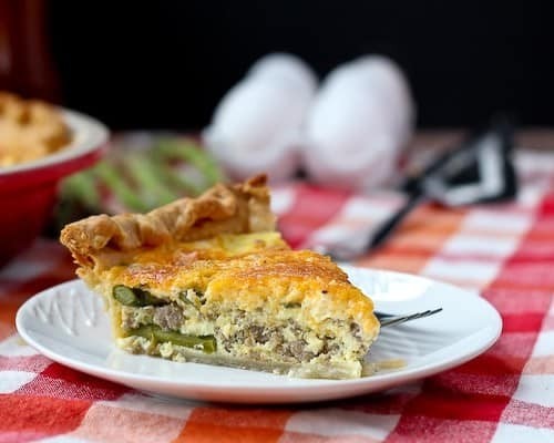 Slice of quiche on a round white plate. Eggs and fresh asparagus in the background.