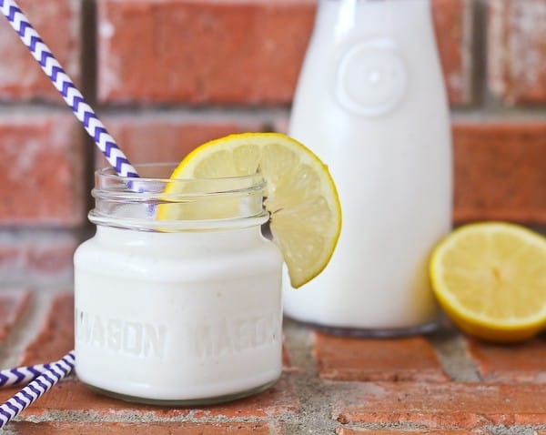 Short jar of a white smoothie with a purple and white straw, garnished with a lemon. Brick background.