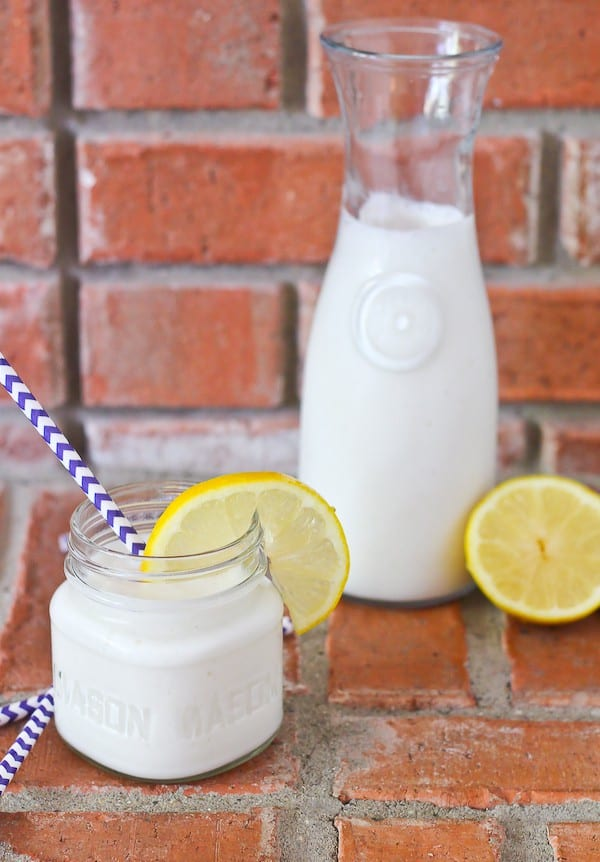 Short jar and large pitcher of a creamy lemon smoothie, light yellow in color.