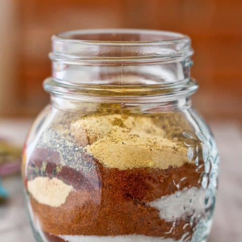 Clear glass jar with layered seasoning ingredients.