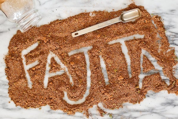 "Seasoning spread on on white marble surface, with the word ""fajita"" spelled out in it."