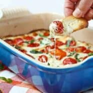 Piece of bread dipping into melted cheese and warm tomatoes.