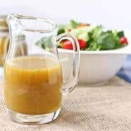 Front view of small clear glass pitcher containing honey mustard vinaigrette, with salad in background.