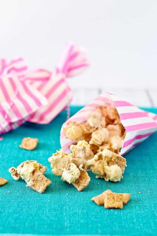 Cinnamon popcorn spilling out of pink striped treat bag onto turquoise cloth surface.