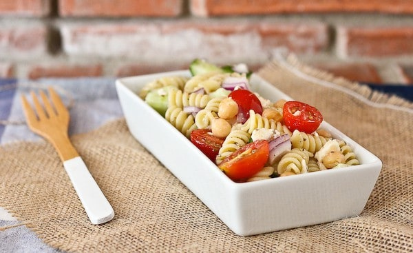 Front view of pasta in rectangular dish with bamboo fork on burlap place mat.