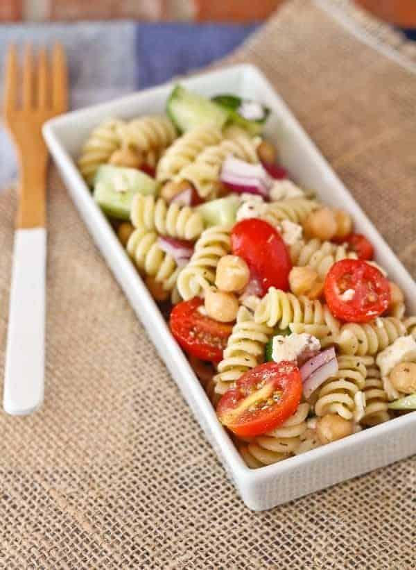 Serving of pasta salad in rectangular white dish, on burlap cloth.